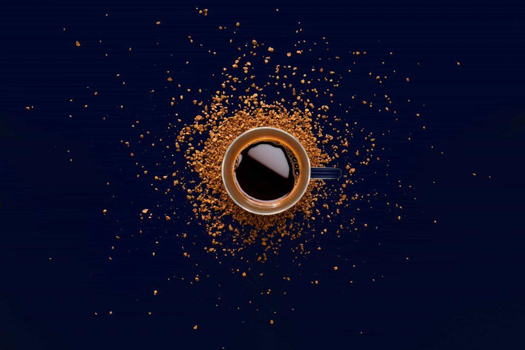 café rodeado de granos de café