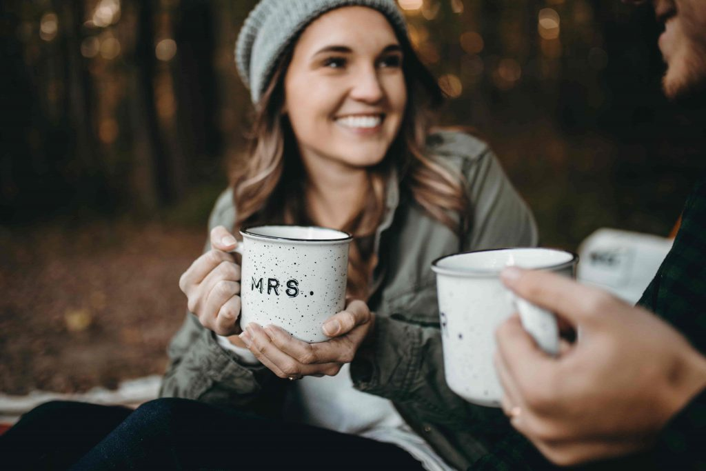 chica sonriente mientras bebe café caliente