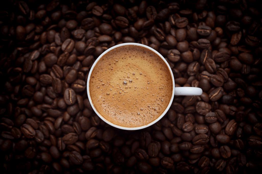 tazá de café con granos de café de fondo