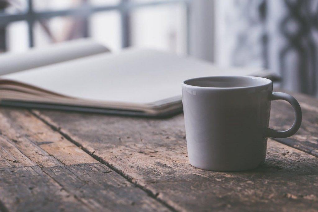 café sobre mesa con libro