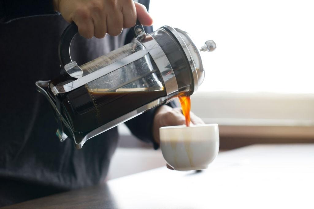 echando café de prensa francesa en taza