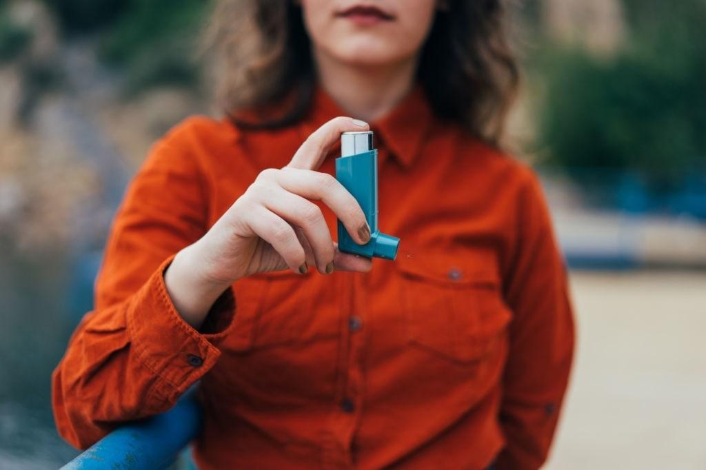 mujer sujetando aparato de asma